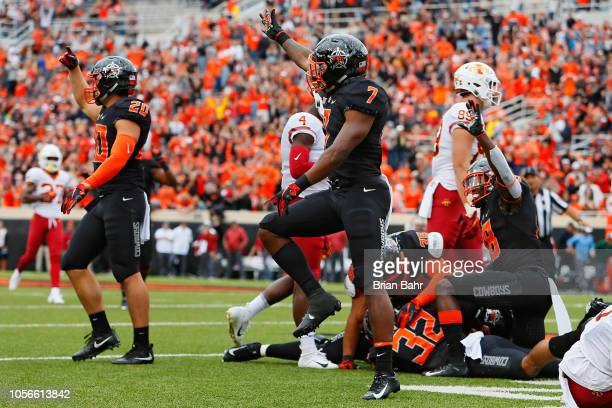 Malcolm Rodriguez and Justice Hill of the Oklahoma State Cowboys celebrate a fumble recovery by Amen Ogbongbemiga against defensive back De'Monte...