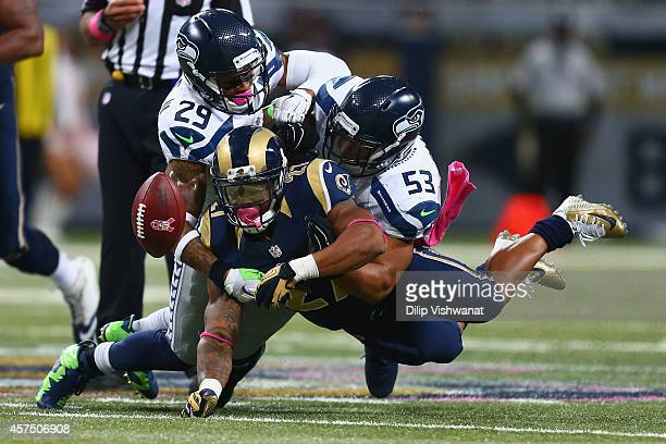Malcolm Smith and Earl Thomas of the Seattle Seahawks force Tre Mason of the St Louis Rams to fumble the ball in the fourth quarter at the Edward...
