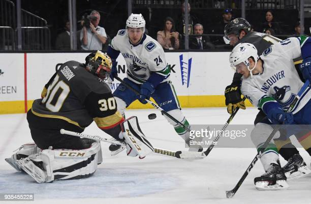 Malcolm Subban of the Vegas Golden Knights blocks a shot by Nic Dowd of the Vancouver Canucks as Reid Boucher looks on in the third period of their...