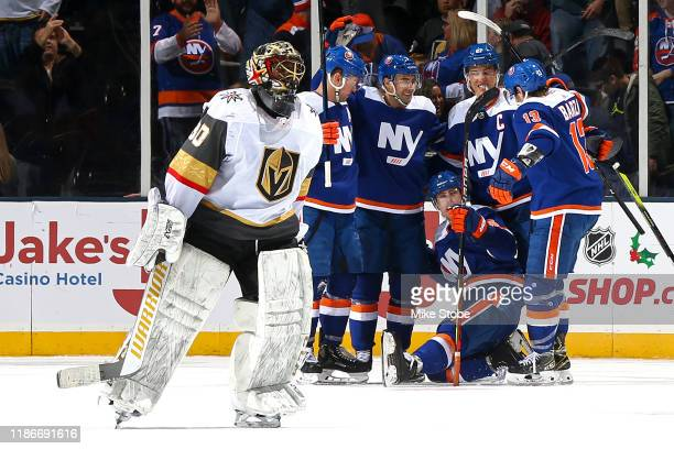 Malcolm Subban of the Vegas Golden Knights skates off the ice as Ryan Pulock of the New York Islanders is congratulated by his teammates after...