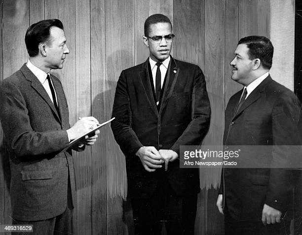 Malcolm X standing with two men 1964