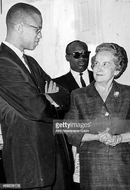 Malcolm X with crossed arms talking to a woman May 1 1963
