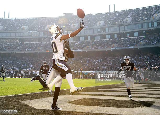 Malcom Floyd of the San Diego Chargers jumps up for a pass in the endzone at Oco Coliseum on January 1 2012 in Oakland California Stanford Routt of...
