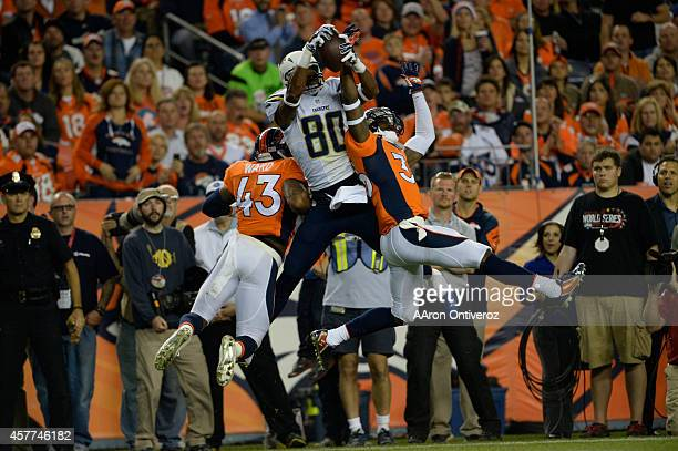 Malcom Floyd of the San Diego Chargers makes a catch for a first down between TJ Ward of the Denver Broncos and Kayvon Webster of the Denver Broncos...