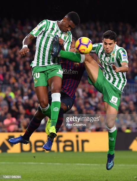 Malcom of Barcelona attempts to win a header while being challenged by Junior Firpo of Real Betis and Marc Bartra of Real Betis during the La Liga...