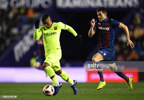 Malcom of Barcelona is chased by Sergio Postigo of Levante during the Copa del Rey Round of 16 match between Levante and FC Barcelona at Ciutat de...