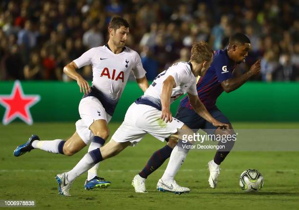 Malcom of Barcelona plays the ball toward goal as Ben Davies and Oliver Skipp of Tottenham Hotspur give pursuit during the second half of their...