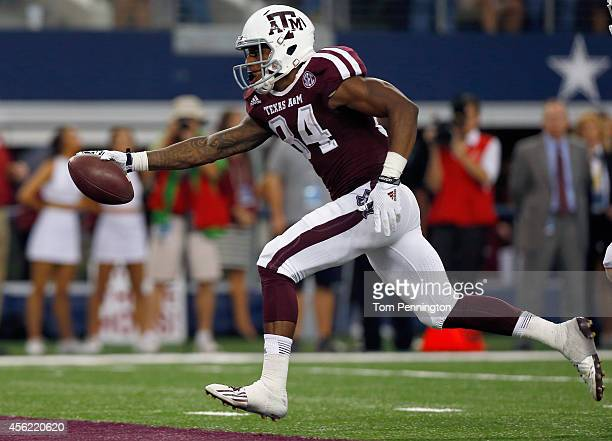 Malcome Kennedy of the Texas A&M Aggies scores the game winning touchdown against the Arkansas Razorbacks in overtime of the Southwest Classic at...