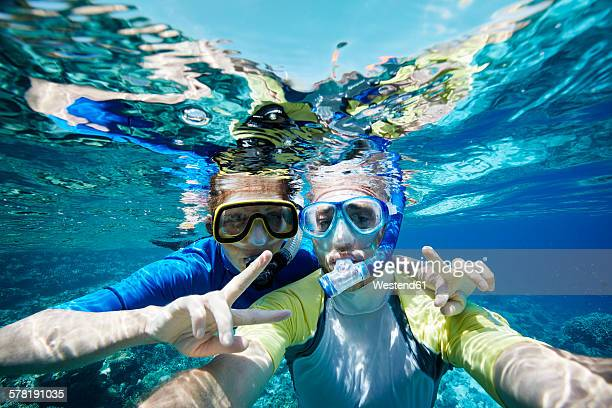 maldives, portrait of couple snorkeling in the indian ocean - snorkeling stock pictures, royalty-free photos & images