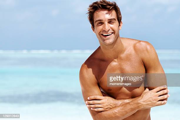 Maldives, Portrait of happy shirtless young male standing with folded hands at beach