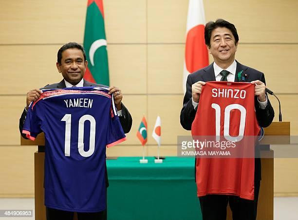Maldives President Abdulla Yameen Abdul Gayoom and Japanese Prime Minister Shinzo Abe show soccer shirts following summit talks at the latter's...