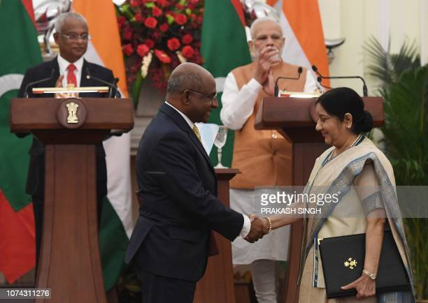 Maldives President Ibrahim Mohamed Solih and India Prime Minister Narendra Modi applaud as India Foreign Minister Sushma Swaraj shakes hands with...