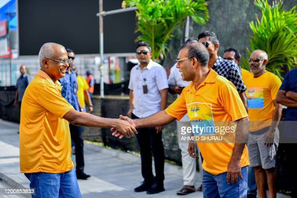 Maldives President Ibrahim Mohamed Solih of Maldives Democratic Party shakes hands as he takes part in a campaign event for the upcoming Local...