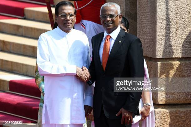Maldives President Ibrahim Mohamed Solih shakes hands with Sri Lankan President Maithripala Sirisena during a welcoming ceremony at the Presidential...