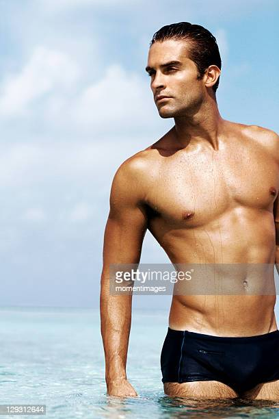 Maldives, Sexy young man in swim trunks standing in the sea