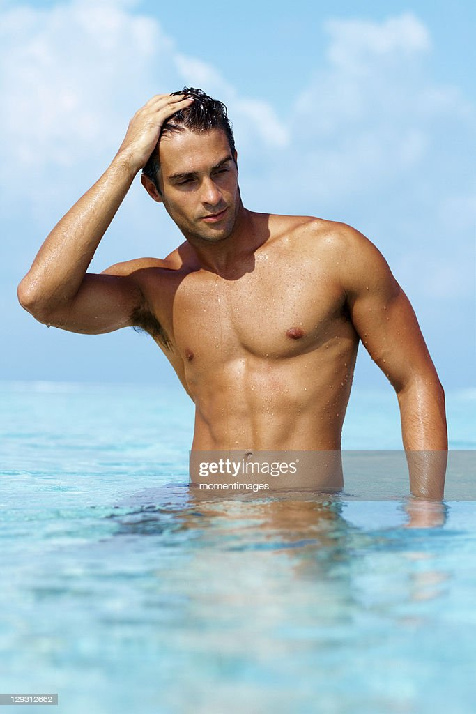 Maldives, Smart young guy taking a bath in the ocean : Stock Photo