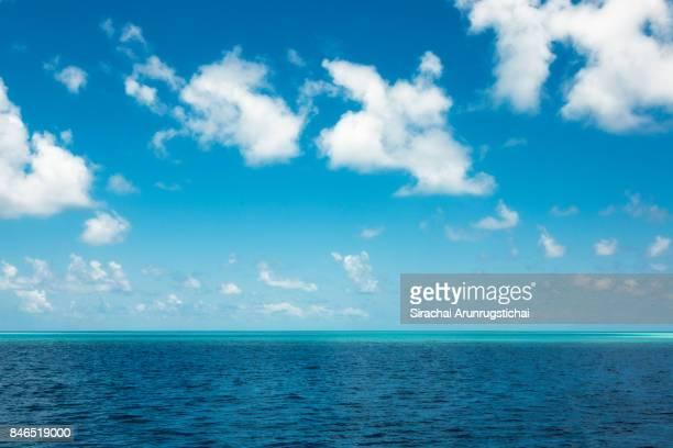 maldivian atoll in deep blue sea under cloudy sky. - linha do horizonte sobre água - fotografias e filmes do acervo