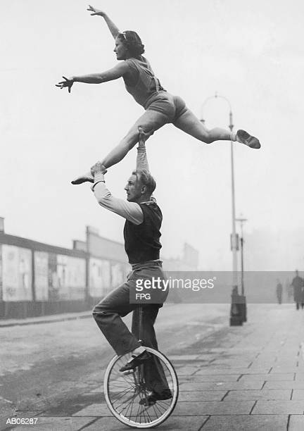 Male acrobat on unicycle supporting woman in air (B&W)