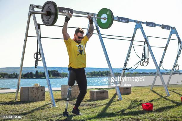 male adaptive athlete lifting deadlift while standing against lake at park during sunny day - 障害者スポーツ ストックフォトと画像