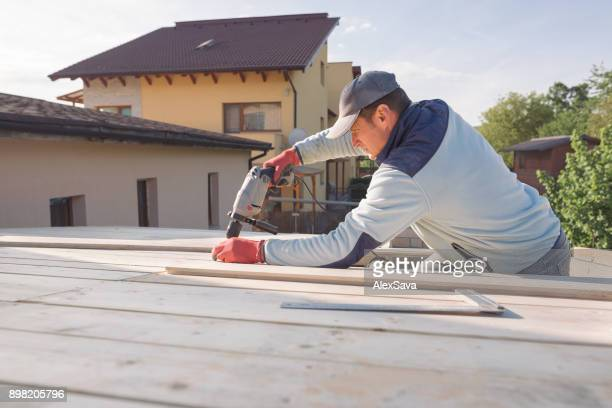 Male adult constructing wooden chalet