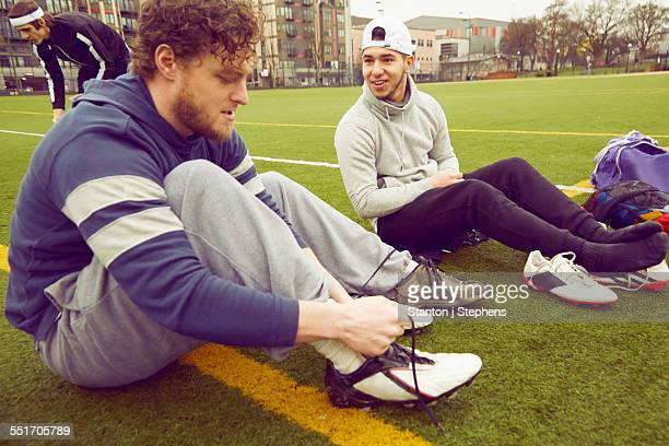 Male adult friends tying boot laces on soccer pitch