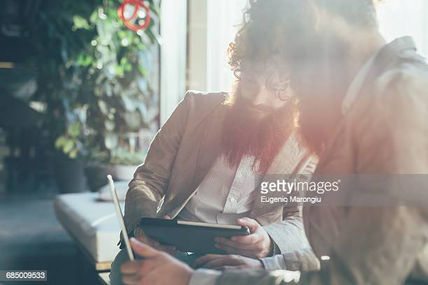 Male adult hipster twins working on digital tablet and laptop in office