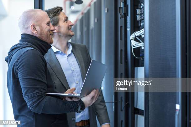 Male Adult Technicians and Manager working together in Server Room Setting