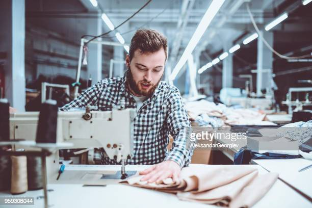 Male Adult Worker Sewing In Textile Factory
