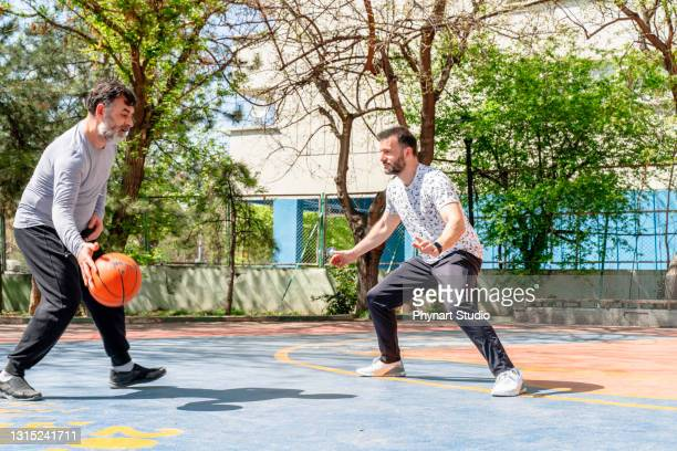 male adults playing basketball outdoors - friendly match stock pictures, royalty-free photos & images