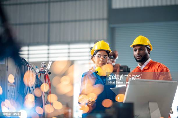 male african engineers and female asian trainee engineer having a meeting in front of industrial robots welder in production line. - factory stock pictures, royalty-free photos & images