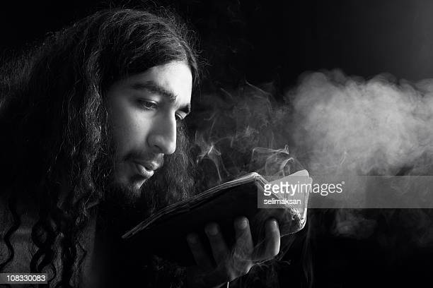 Male Alchemist Blowing Dust Off and Antique Book