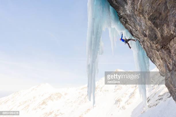 Male alpinist ice climbing on sharp icicles