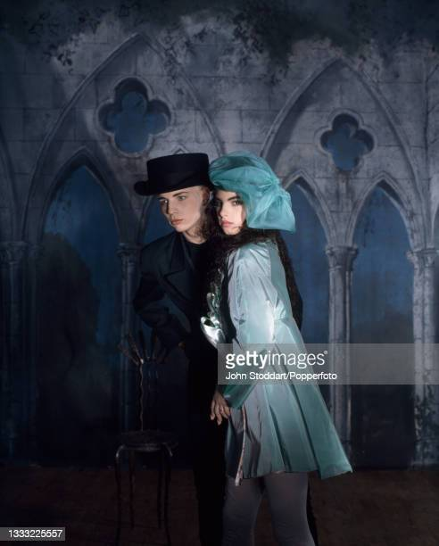 Male and a female fashion model wear outfits by John Galliano, the man wears a short black frock coat and a black felt hat, the woman wears an aqua...