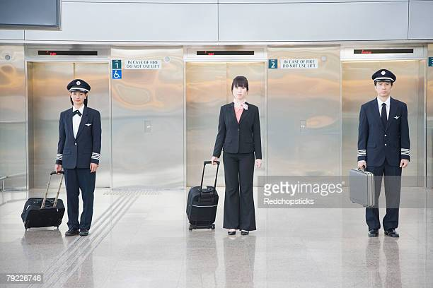 Male and a female pilot standing with a female cabin crew in front of elevators