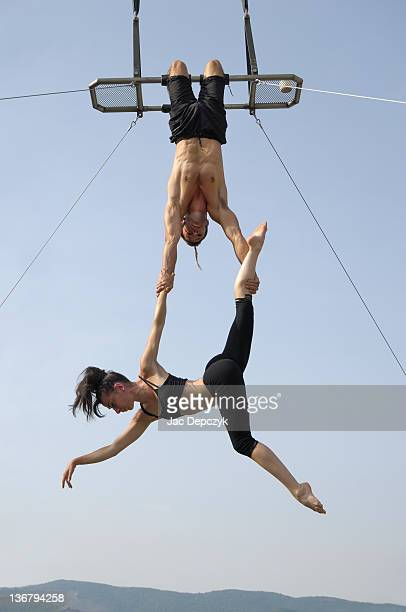 Male and female acrobats perform high on trapeze