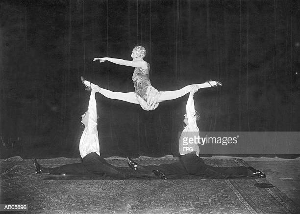 Male and female acrobats performing splits, profile (B&W)