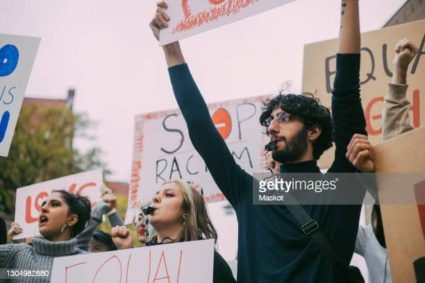male and female activist participating in anti-racism protest - civil rights stock pictures, royalty-free photos & images