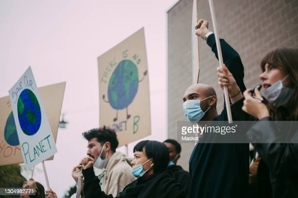 male and female activist protesting for environmental issues during pandemic - politiek en staatsbestuur stockfoto's en -beelden