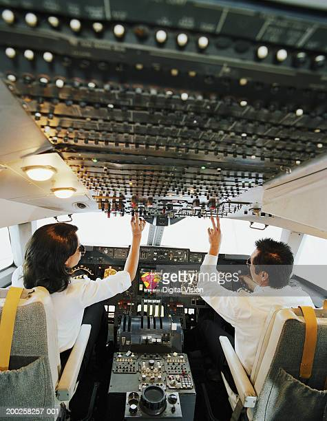male and female aeroplane pilot, operating controls, rear view - co pilot stock photos and pictures