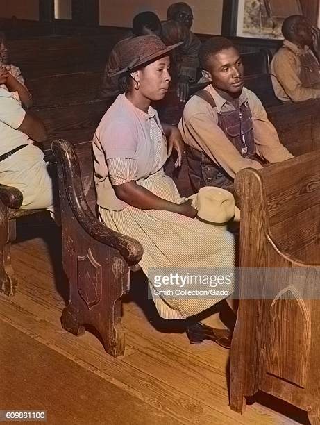 Male and female AfricanAmerican farmers sitting in pews at a church during a Farm Security Administration meeting of borrowers in a church near...