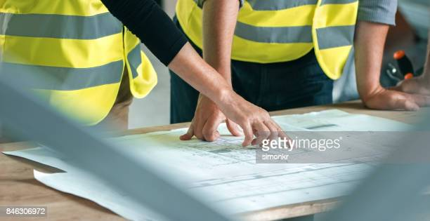 Male and female architect going through construction plans