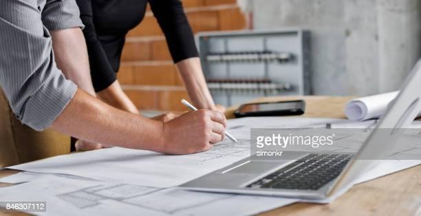 männliche und weibliche architekt baupläne durchlaufen - technische zeichnung stock-fotos und bilder