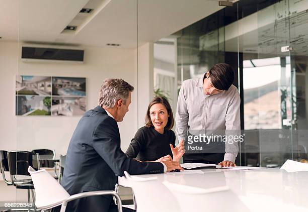 Male and female architects discussing at desk