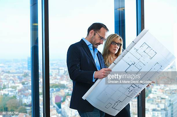 Male and female architects looking at plans in front of office window with Brussels cityscape, Belgium