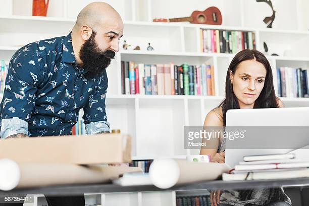 Male and female architects using laptop at home office