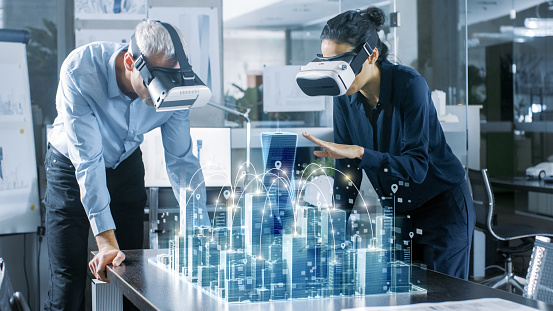 Male and Female Architects Wearing  Augmented Reality Headsets Work with 3D City Model. High Tech Office Professional People Use Virtual Reality Modeling Software Application. 921019710