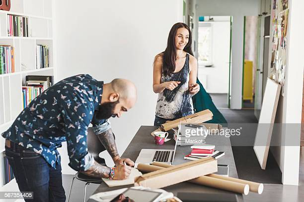 Male and female architects working at table