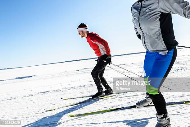 male and female athletes cross-country skiing. - langlaufen stockfoto's en -beelden