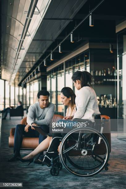 male and female business executive working on laptop with disabled entrepreneur in office corridor - differing abilities female business fotografías e imágenes de stock