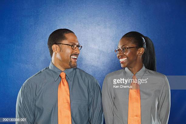male and female business executives in matching shirt and tie, smiling - identical twin stock pictures, royalty-free photos & images